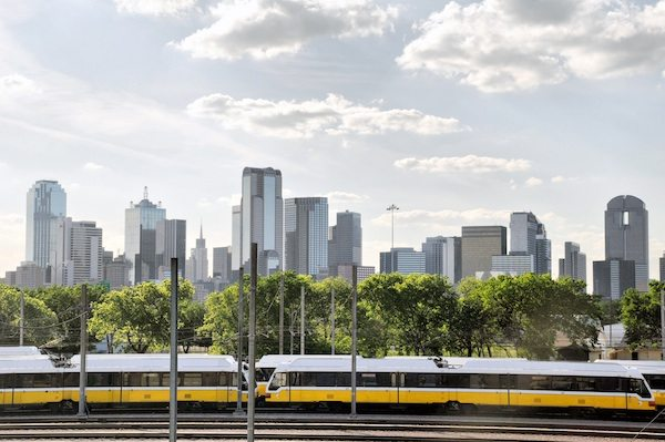 A rapid transit train (DART) with the skyline of Dallas, Texas in the background